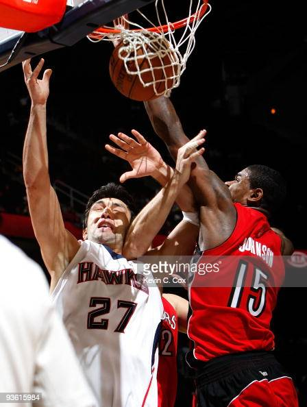 Zaza Pachulia of the Atlanta Hawks draws a foul while driving against Rasho Nesterovic and Amir Johnson of the Toronto Raptors at Philips Arena on...