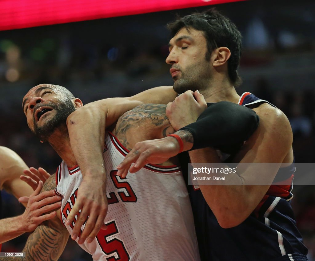 Zaza Pachulia #27 of the Atlanta Hawks hits Carlos Boozer #5 of the Chicago Bulls with his elbow at the United Center on January 14, 2013 in Chicago, Illinois. The Bulls defeated the Hawks 97-58.