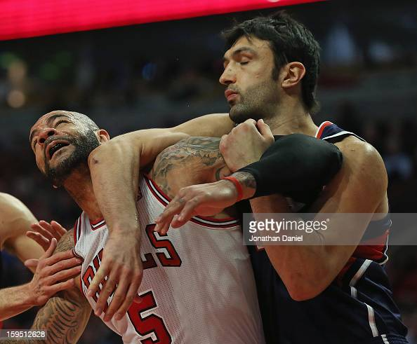 Zaza Pachulia of the Atlanta Hawks hits Carlos Boozer of the Chicago Bulls with his elbow at the United Center on January 14 2013 in Chicago Illinois...