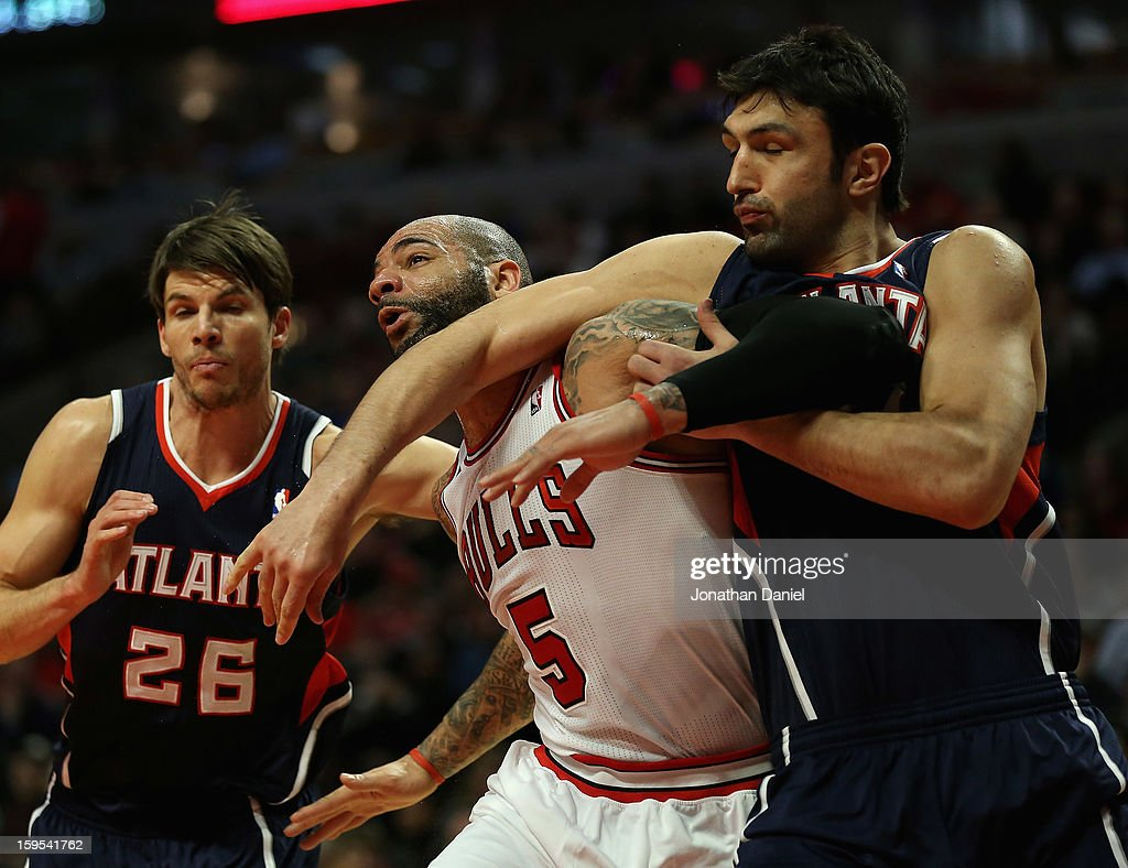 Zaza Pachulia #27 of the Atlanta Hawks hits Carlos Boozer #5 of the Chicago Bulls with his elbow as Kyle Korver #26 defends on a free throw at the United Center on January 14, 2013 in Chicago, Illinois. The Bulls defeated the Hawks 97-58.