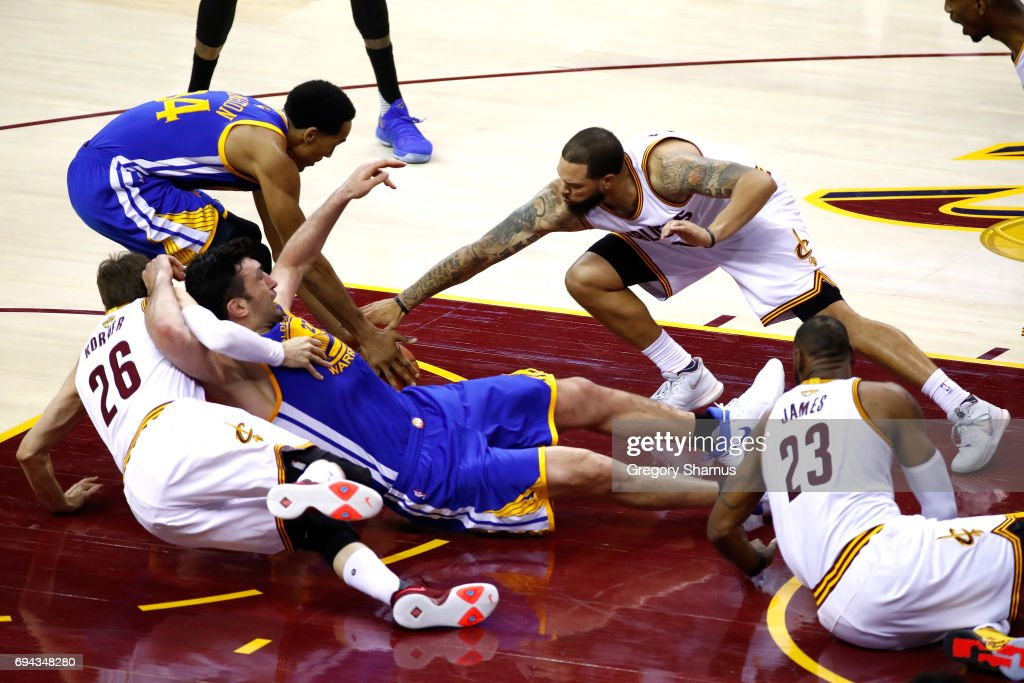 Zaza Pachulia #27 of the Golden State Warriors gets tangled with Kyle Korver #26 and Deron Williams #31 of the Cleveland Cavaliers in the third quarter in Game 4 of the 2017 NBA Finals at Quicken Loans Arena on June 9, 2017 in Cleveland, Ohio.