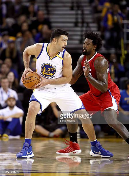 Zaza Pachulia of the Golden State Warriors is guarded by DeAndre Jordan of the Los Angeles Clippers during their preseason game at ORACLE Arena on...