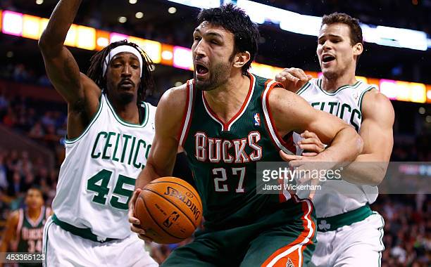 Zaza Pachulia of the Milwaukee Bucks is defneded underneath the basket by Gerald Wallace and Kris Humphries of the Boston Celtics in the second half...