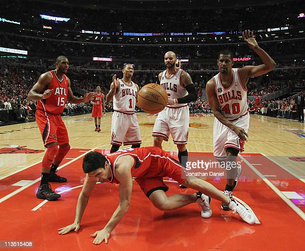 Zaza Puchulia of the Atlanta Hawks hits the floor in front of teammate Al Horford after being fouled by Kurt Thomas of the Chicago Bulls as Derrick...