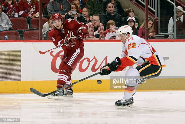 Zbynek Michalek of the Arizona Coyotes passes the puck under the stick of Drew Shore of the Calgary Flames during the third period at Gila River...