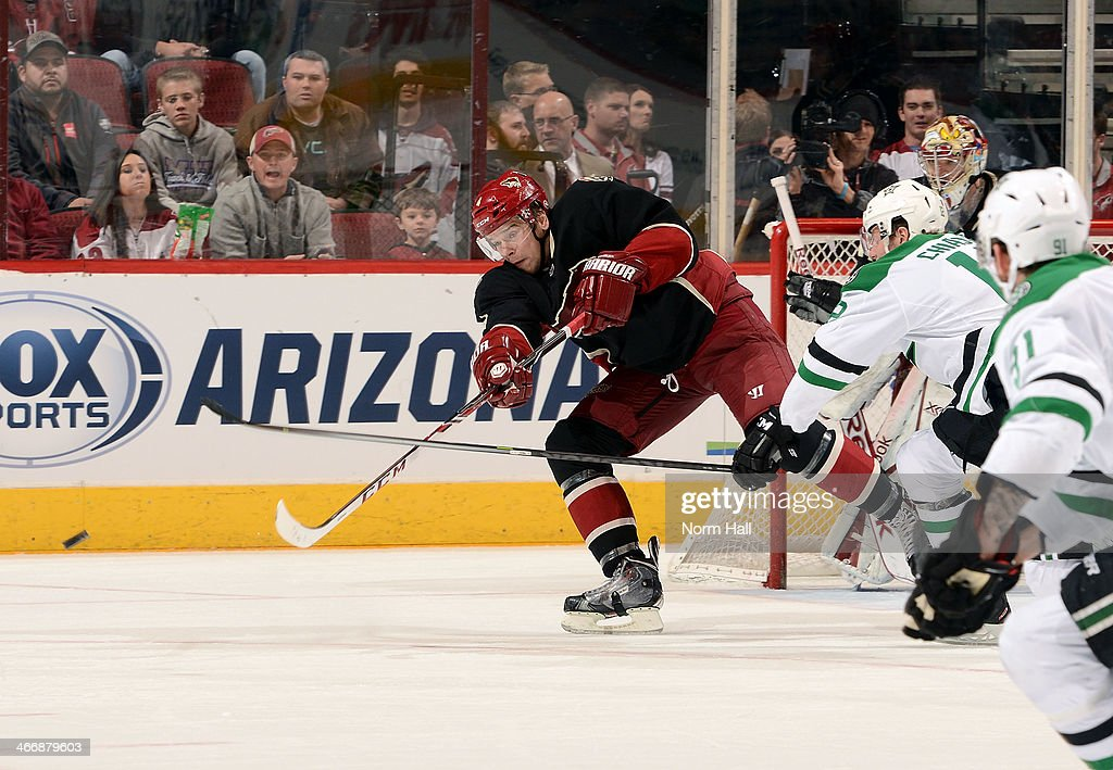 Zbynek Michalek #4 of the Phoenix Coyotes clears the puck away from Alex Chiasson #12 of the Dallas Stars during the third period at Jobing.com Arena on February 4, 2014 in Glendale, Arizona.