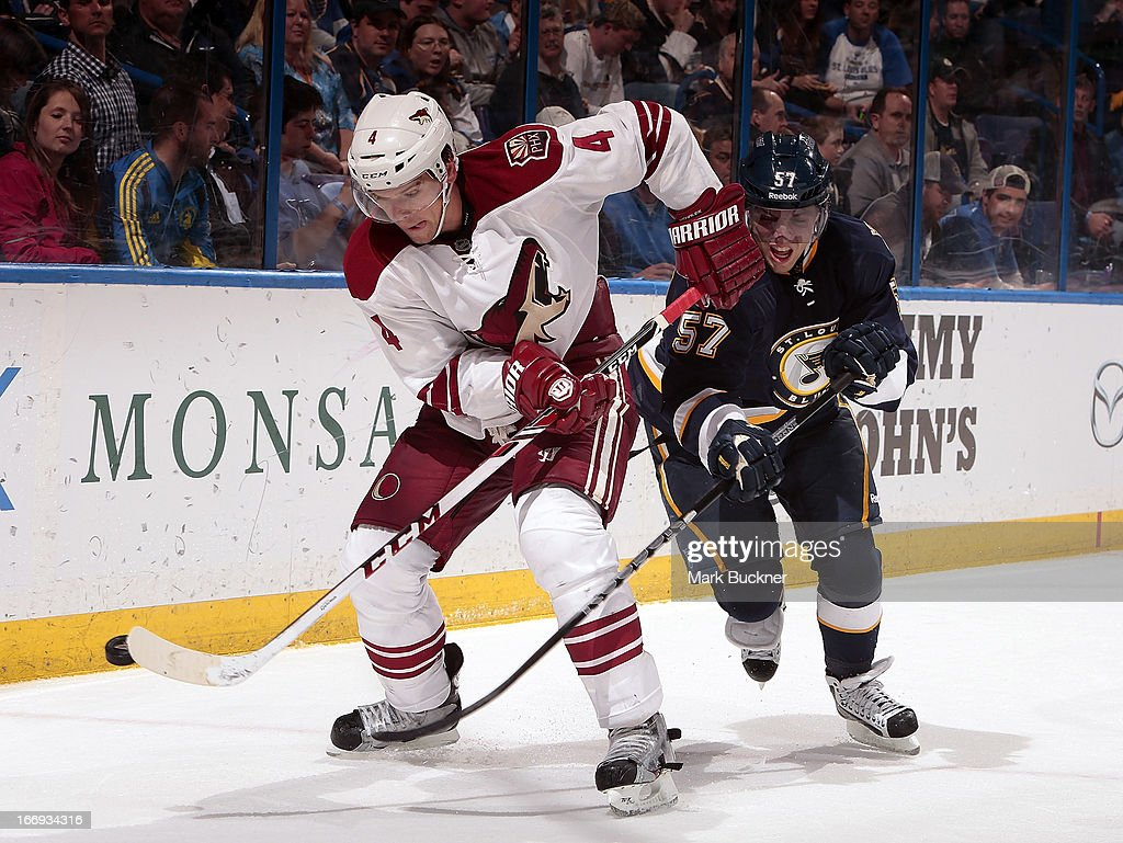 Zbynek Michalek #4 of the Phoenix Coyotes fends off David Perron #57 of the St. Louis Blues as he controls the bouncing puck in an NHL game on April 18, 2013 at Scottrade Center in St. Louis, Missouri.