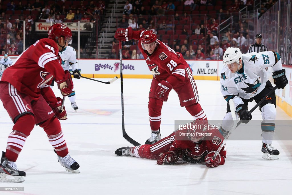 Zbynek Michalek #4 of the Phoenix Coyotes is penalized for delay of game as he covers the puck pressured by Tommy Wingels #57 of the San Jose Sharks during the third period of the preseason NHL game at Jobing.com Arena on September 27, 2013 in Glendale, Arizona.