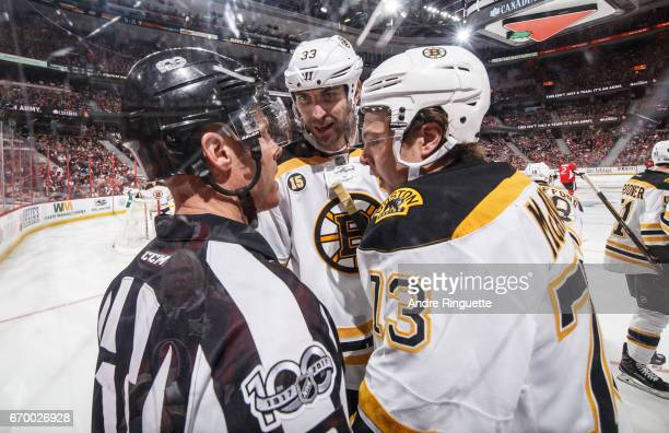 Zdeno Chara and Charlie McAvoy of the Boston Bruins have words with an official during in Game Two of the Eastern Conference First Round against the...