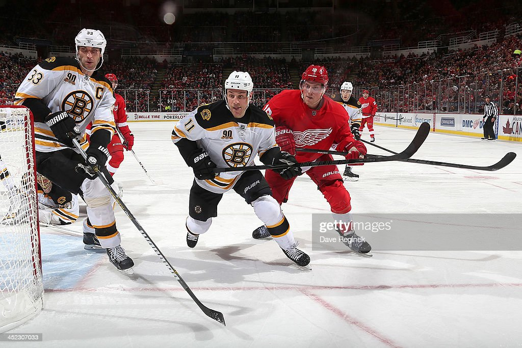 <a gi-track='captionPersonalityLinkClicked' href=/galleries/search?phrase=Zdeno+Chara&family=editorial&specificpeople=203177 ng-click='$event.stopPropagation()'>Zdeno Chara</a> #33 and <a gi-track='captionPersonalityLinkClicked' href=/galleries/search?phrase=Gregory+Campbell&family=editorial&specificpeople=640895 ng-click='$event.stopPropagation()'>Gregory Campbell</a> #11 of the Boston Bruins race Joakim Andersson #18 of the Detroit Red Wings for the puck behind the net during an NHL game at Joe Louis Arena on November 27, 2013 in Detroit, Michigan.