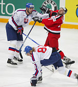 Zdeno Chara of Slovakia keeps Mark Streit of Switzerland at bay as Slovak Marian Hossa takes control of the puck in the teams' quarter finals match...