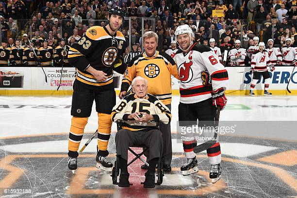 Zdeno Chara of the Boston Bruins and Andy Greene the New Jersey Devils pose with alumni players Bobby Orr and Milt Schmidt before the season opener...