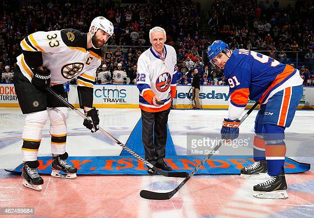 Zdeno Chara of the Boston Bruins and John Tavares of the New York Islanders take part in a ceremonial puck drop with former New York Islander and...