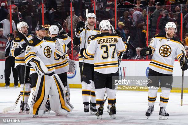 Zdeno Chara of the Boston Bruins celebrates their overtime win against the Ottawa Senators with teammates Patrice Bergeron Joe Morrow Anton Khudobin...