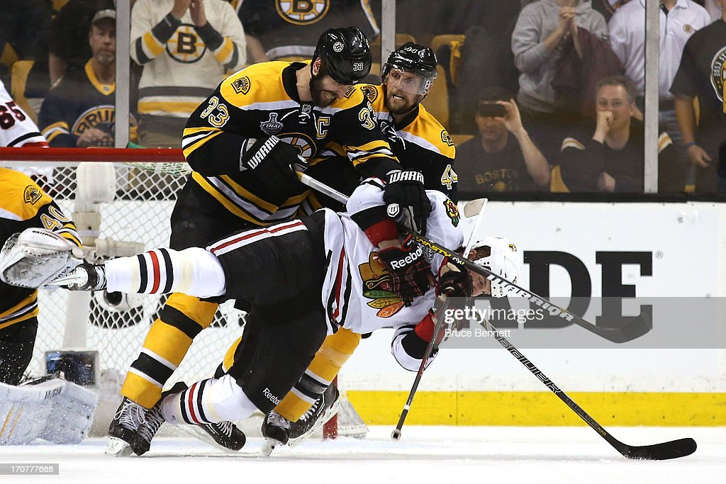 <a gi-track='captionPersonalityLinkClicked' href=/galleries/search?phrase=Zdeno+Chara&family=editorial&specificpeople=203177 ng-click='$event.stopPropagation()'>Zdeno Chara</a> #33 of the Boston Bruins checks <a gi-track='captionPersonalityLinkClicked' href=/galleries/search?phrase=Bryan+Bickell&family=editorial&specificpeople=241498 ng-click='$event.stopPropagation()'>Bryan Bickell</a> #29 of the Chicago Blackhawks to the ice late in the game in Game Three of the 2013 NHL Stanley Cup Final at TD Garden on June 17, 2013 in Boston, Massachusetts.
