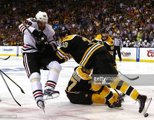 Zdeno Chara of the Boston Bruins collides with Michal Handzus of the Chicago Blackhawks in Game Three of the 2013 NHL Stanley Cup Final at TD Garden...