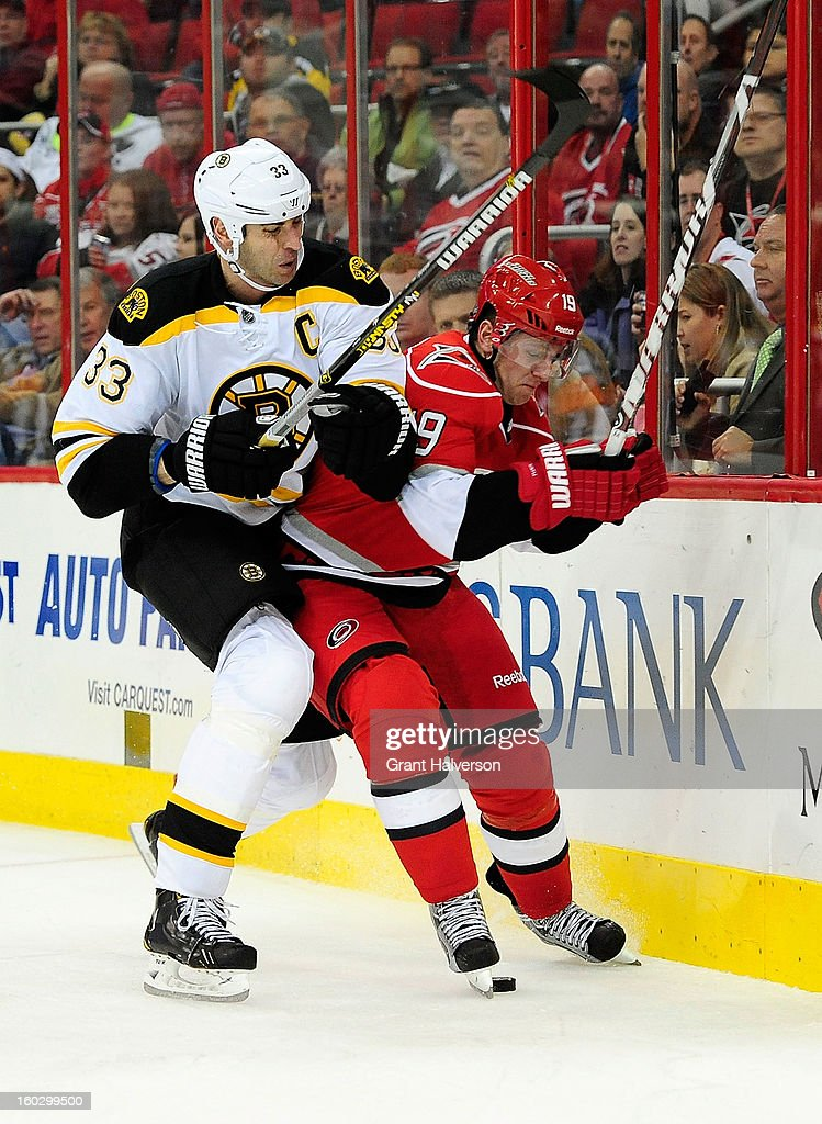 Zdeno Chara #33 of the Boston Bruins drives Jiri Tlusty #19 of the Carolina Hurricanes inot the boards during play at PNC Arena on January 28, 2013 in Raleigh, North Carolina.