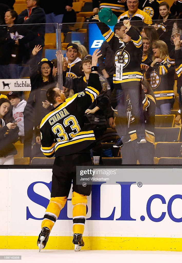 Zdeno Chara #33 of the Boston Bruins gives a hat to a young fan following their 3-1 win against the New York Rangers during the season opener game on January 19, 2013 at TD Garden in Boston, Massachusetts.