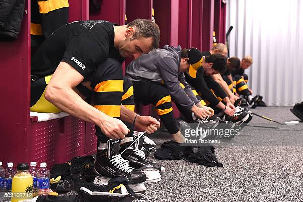 Zdeno Chara of the Boston Bruins laces up his skates in the locker room prior to the 2016 Bridgestone NHL Classic against the Montreal Canadiens at...