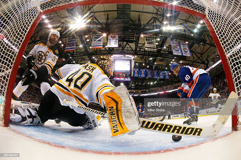 Zdeno Chara #33 of the Boston Bruins looks on as Tuukka Rask #40 of the Boston Bruins makes a stick save on a shot from Michael Grabner #40 of the New York Islanders at Nassau Veterans Memorial Coliseum on January 29, 2015 in Uniondale, New York.