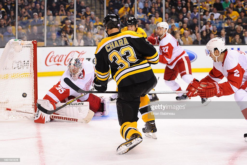<a gi-track='captionPersonalityLinkClicked' href=/galleries/search?phrase=Zdeno+Chara&family=editorial&specificpeople=203177 ng-click='$event.stopPropagation()'>Zdeno Chara</a> #33 of the Boston Bruins shoots the puck against <a gi-track='captionPersonalityLinkClicked' href=/galleries/search?phrase=Jimmy+Howard&family=editorial&specificpeople=2118637 ng-click='$event.stopPropagation()'>Jimmy Howard</a> #35 of the Detroit Red Wings at the TD Garden on October 5, 2013 in Boston, Massachusetts.