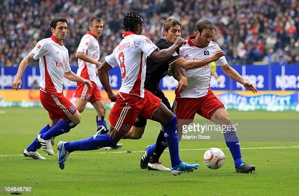 Ze Roberto and Joris Mathijsen of Hamburg and Clemens Walch of Kaiserslautern compete for the ball during the Bundesliga match between Hamburger SV...