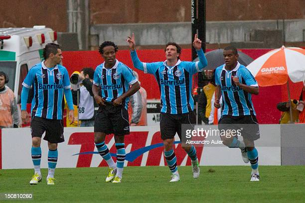Ze Roberto Elano and Fernando of Gremio celebrate a scored goal by Elano against Internacional during a match as part of Brasileiro Championship at...