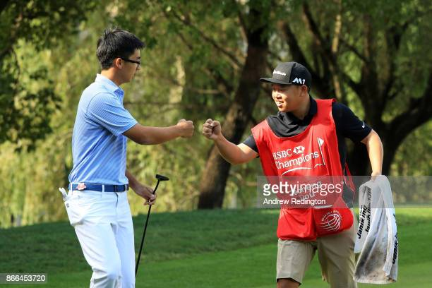 Zecheng Dou of China and his caddie celebrate a birdie on the 13th green during the first round of the WGC HSBC Champions at Sheshan International...