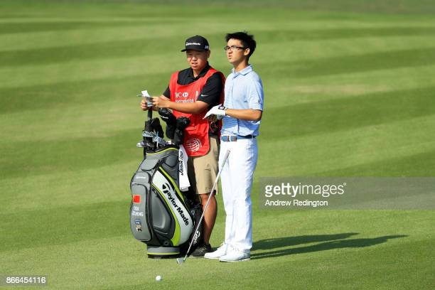 Zecheng Dou of China prepares to play a shot with his caddie on the 13th hole during the first round of the WGC HSBC Champions at Sheshan...