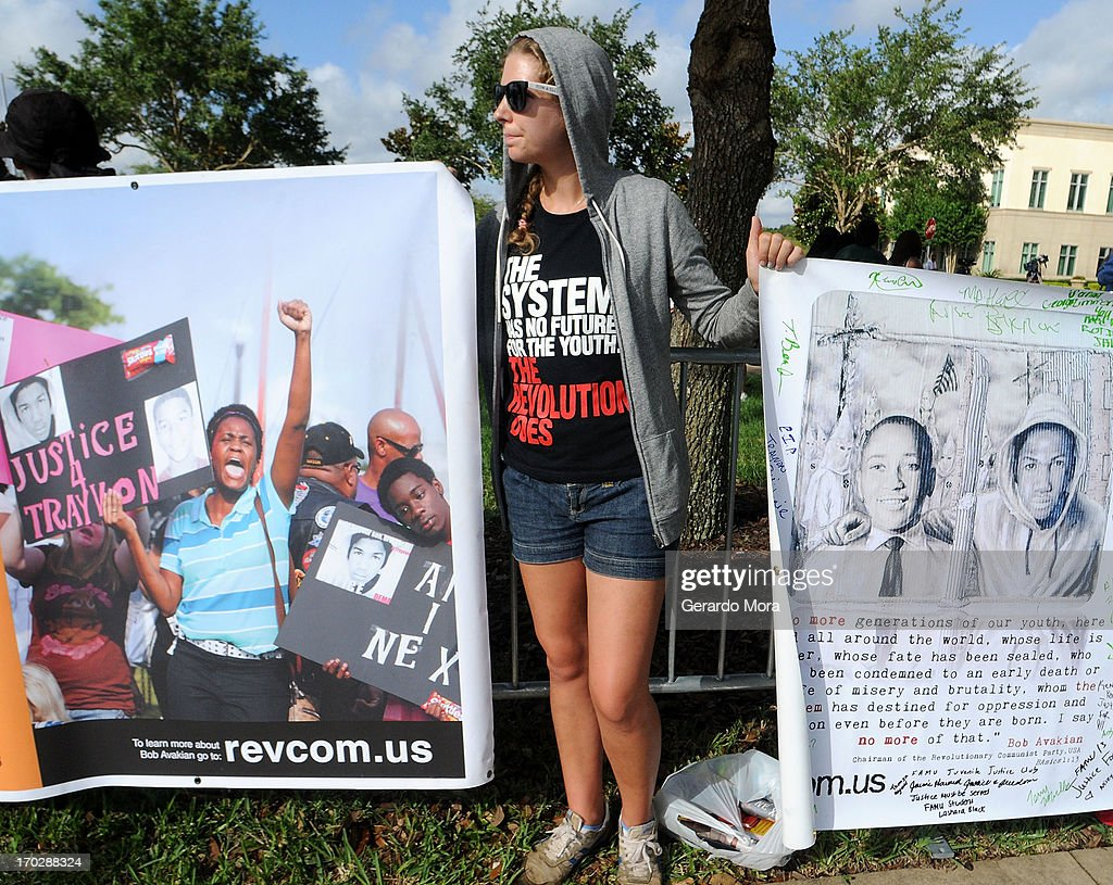 Zee of Atlanta, member of the Revolutionary Communist Party holds signs in support of Trayvon Martin's family outside the Seminole County Courthouse during the first day of trial for George Zimmerman on June 10, 2013 in Sanford, Florida. Jury selection will begin today as Zimmerman is charged with the second-degree murder of an unarmed teenager, Trayvon Martin.