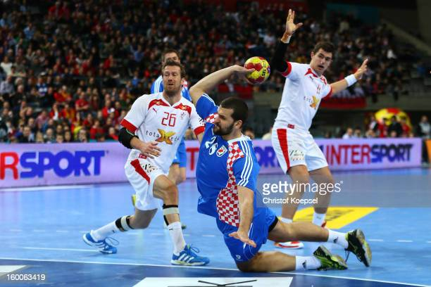 Zeljko Musa of Croatia scores a goal against Kasper Nielsen of Denmark during Men's Handball World Championship 2013 semi final match between Denmark...