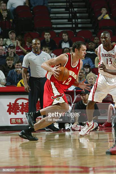 Zeljko Rebraca of the Atlanta Hawks moves the ball against Kelvin Cato of the Houston Rockets during the game at Toyota Center on February 22 2004 in...