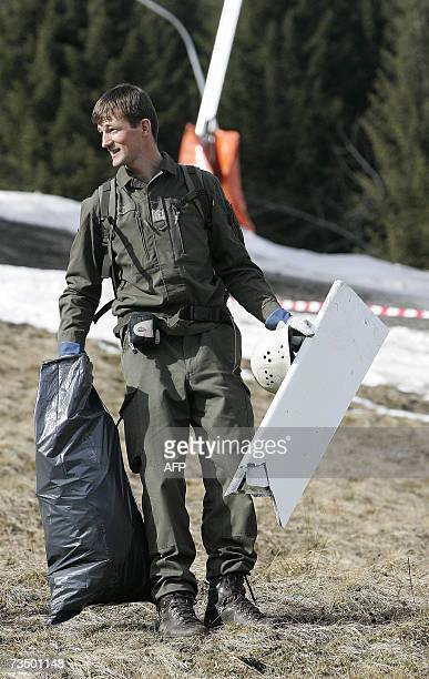 A member of the Austrian army carries 06 March 2007 parts of a wreckage after a helicopter and a small plane collided in midair 05 March 2007 near a...