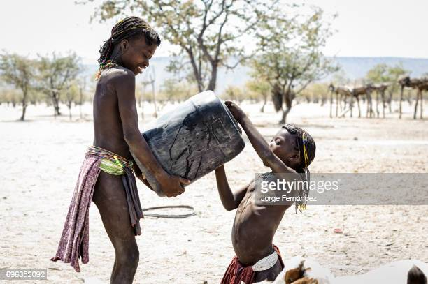 Zemba girl helping another girl drinking from a jerry can Zembas are a bantu tribe family of the Himbas who migrated into what today is Namibia a few...