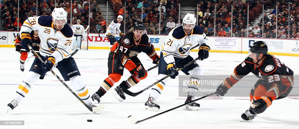 Zemgus Girgensons and Drew Stafford the Buffalo Sabres battle for the puck against Hampus Lindholm and Francois Beauchemin of the Anaheim Ducks on...