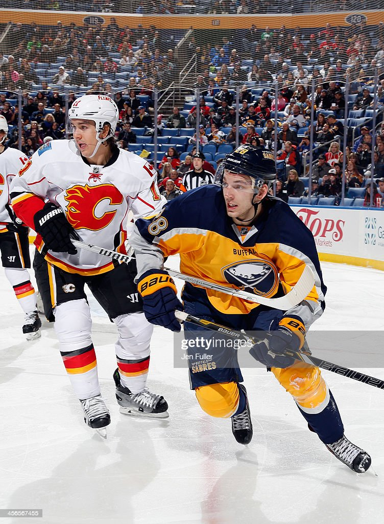 Zemgus Girgensons #28 of the Buffalo Sabres and Mikael Backlund #11 of the Calgary Flames follow the play at First Niagara Center on December 14, 2013 in Buffalo, New York.