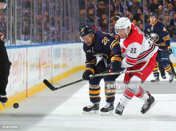 Zemgus Girgensons of the Buffalo Sabres battles for the puck with Brett Pesce of the Carolina Hurricanes during an NHL game on November 18 2017 at...