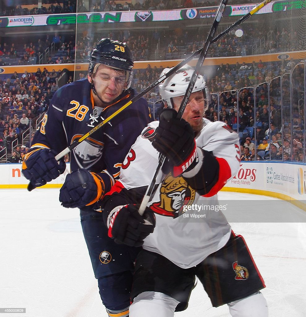 <a gi-track='captionPersonalityLinkClicked' href=/galleries/search?phrase=Zemgus+Girgensons&family=editorial&specificpeople=8050732 ng-click='$event.stopPropagation()'>Zemgus Girgensons</a> #28 of the Buffalo Sabres checks <a gi-track='captionPersonalityLinkClicked' href=/galleries/search?phrase=Marc+Methot&family=editorial&specificpeople=2216900 ng-click='$event.stopPropagation()'>Marc Methot</a> #3 of the Ottawa Senators on December 10, 2013 at the First Niagara Center in Buffalo, New York. Buffalo won, 2-1.