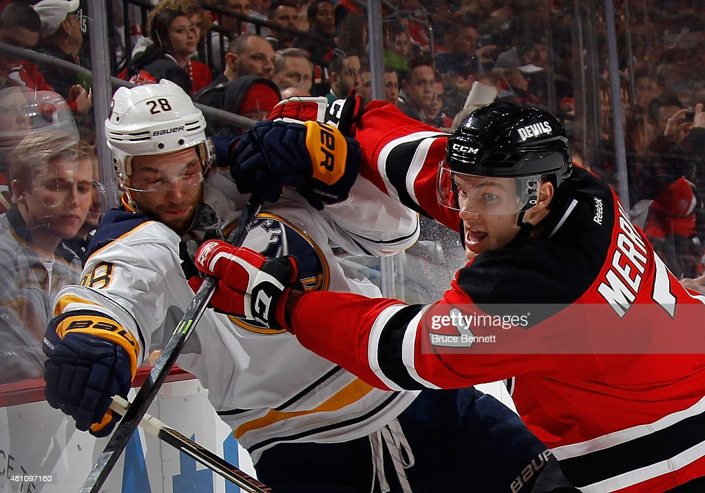 Zemgus Girgensons of the Buffalo Sabres is hit into the boards by Jon Merrill of the New Jersey Devils during the first period at the Prudential...