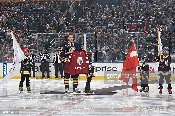 Zemgus Girgensons of the Buffalo Sabres is presented with a team Latvia jersey during a pregam ceremony for the 2014 Sochi Olympics before the Sabres...