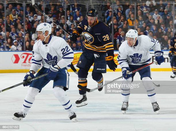 Zemgus Girgensons of the Buffalo Sabres jumps between Nikita Zaitsev and Connor Brown of the Toronto Maple Leafs during an NHL game at the KeyBank...