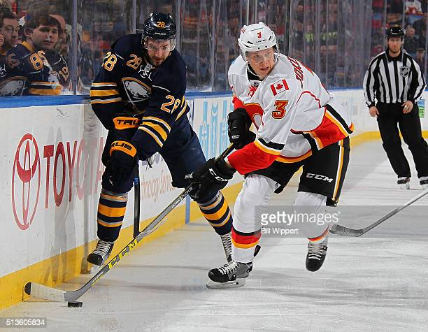 Zemgus Girgensons of the Buffalo Sabres looks to take the puck away from Jyrki Jokipakka of the Calgary Flames during an NHL game on March 3 2016 at...
