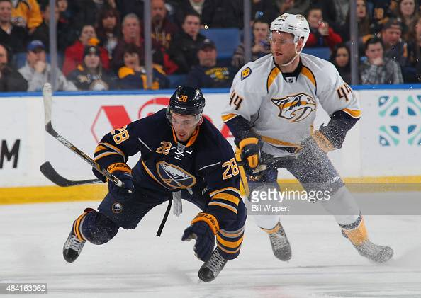 Zemgus Girgensons of the Buffalo Sabres loses his balance while making a quick stop alongside Cody Franson of the Nashville Predators on February 22...