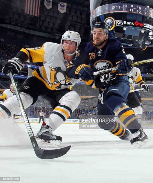 Zemgus Girgensons of the Buffalo Sabres playing in his NHL 300th game battles for the puck against Brian Dumoulin of the Pittsburgh Penguins on...