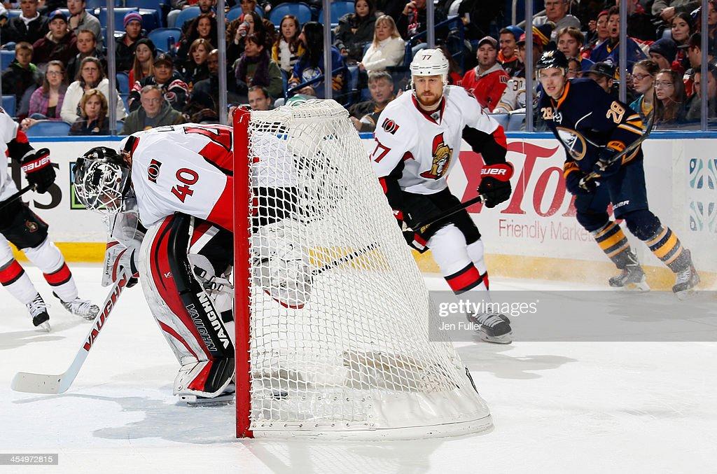 Zemgus Girgensons #28 of the Buffalo Sabres scores a second period goal against Robin Lehner #40 of the Ottawa Senators as Joe Corvo #77 of Ottawa follows the play at First Niagara Center on December 10, 2013 in Buffalo, New York.