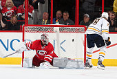 Zemgus Girgensons of the Buffalo Sabres scores the winning goal of the shootout on Cam Ward during their NHL game at PNC Arena on October 14 2014 in...