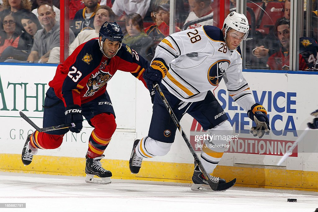 Zemgus Girgensons #28 of the Buffalo Sabres skates with the puck against Scott Gomez #23 of the Florida Panthers at the BB&T Center on October 25, 2013 in Sunrise, Florida.