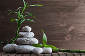 Zen balance stones and bamboo plant on the straw mat