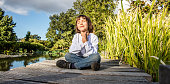 zen young yoga child cross-legged enjoying meditating alone, closing eyes for relaxation and breathing on a wooden bridge near water with blue sky, low angle view