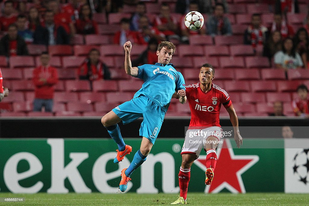 Zenit's defender <a gi-track='captionPersonalityLinkClicked' href=/galleries/search?phrase=Nicolas+Lombaerts&family=editorial&specificpeople=4332055 ng-click='$event.stopPropagation()'>Nicolas Lombaerts</a> jumps higher that Benfica's forward Lima during the Champions League match between Benfica and Zenit on September 16, 2014 in Lisbon, Portugal.